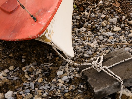 Boat tied up on the shore to a rock